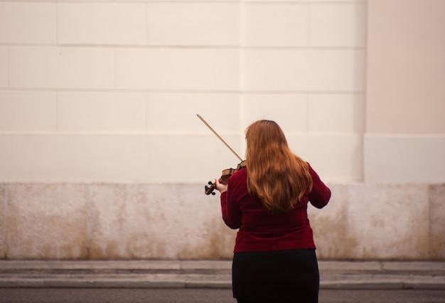 Weiblicher violinist, der in der straße spielt