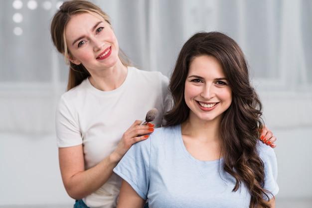 Weiblicher visagiste mit dem kunden, der an der kamera lächelt