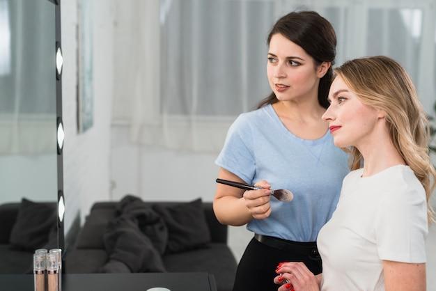 Weiblicher visagiste mit dem kunden, der im spiegel schaut