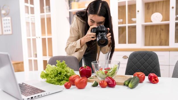 Weiblicher vlogger, der bilder mit kamera macht