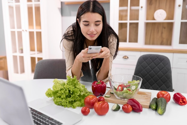Weiblicher vlogger, der bilder mit smartphone macht