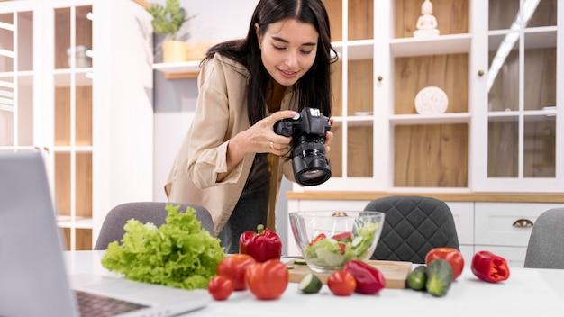 Weiblicher vlogger zu hause, der bilder mit kamera macht