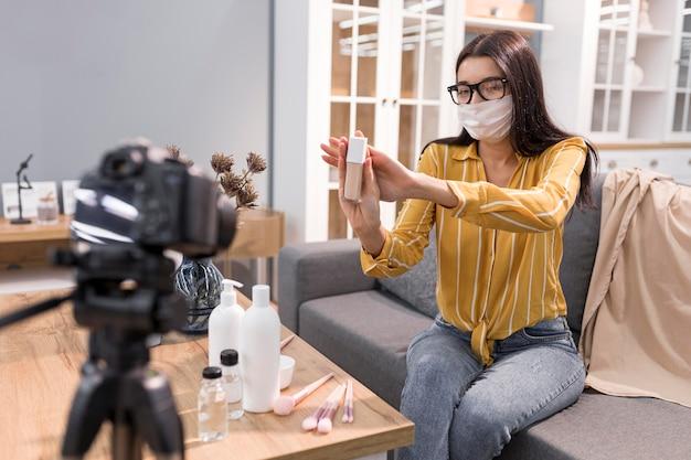 Weiblicher vlogger zu hause mit kamera und gesichtsmaske