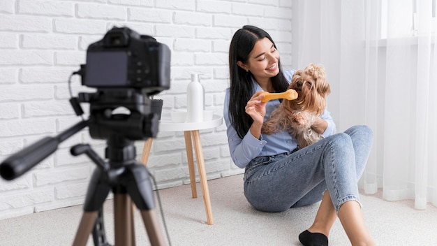 Weiblicher vlogger zu hause mit kamera und hund