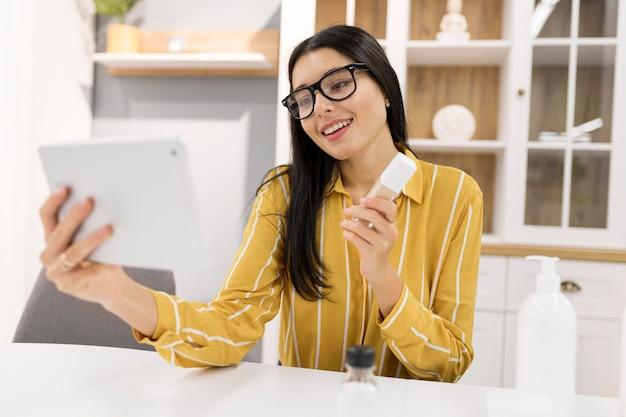 Weiblicher vlogger zu hause mit produkt und tablette