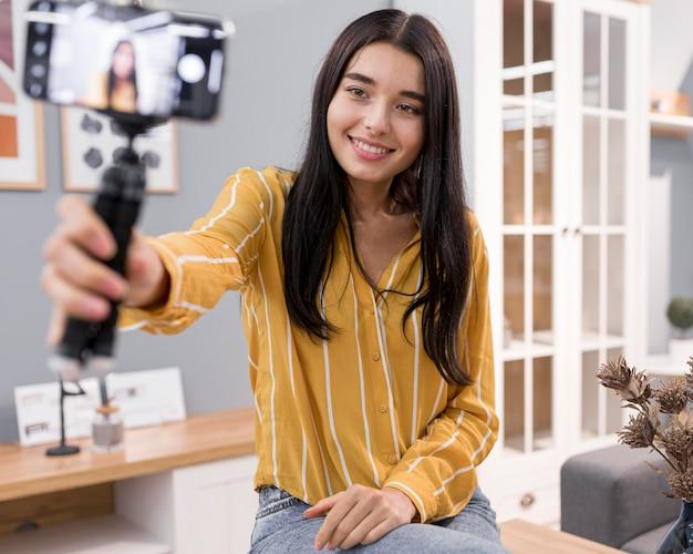 Weiblicher vlogger zu hause mit smartphone