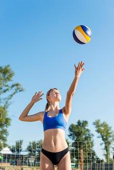 Weiblicher volleyballspieler auf dem strand, der ball dient