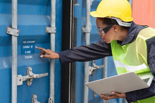 Weiblicher vorarbeiter, der die nummer an der behälterkastentür mit einem laptop am frachtcontainerversand überprüft