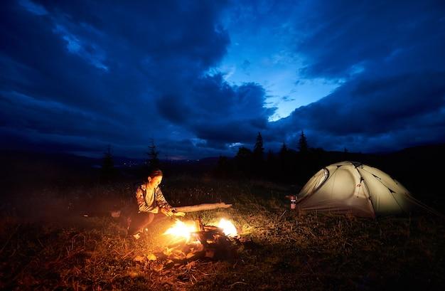Weiblicher wanderer, der am nachtcamping ruht