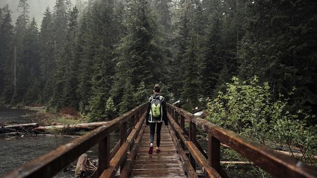 Weiblicher wanderer, der auf die holzbrücke führt in richtung zum wald geht