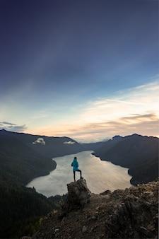 Weiblicher wanderer, der auf die oberseite des berg-sturm-königs olympic national park steht