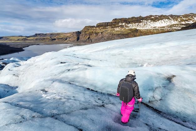 Weiblicher wanderer, der auf gletscher bei solheimajokull geht