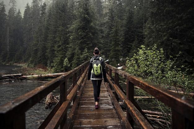 Weiblicher wanderer, der auf holzbrücke geht