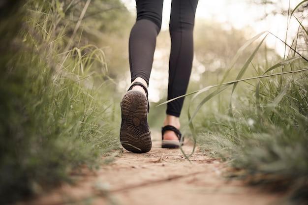 Weiblicher wanderer, der auf schotterweg geht