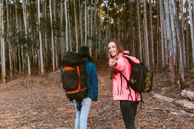 Weiblicher wanderer, der beim gehen mit ihrem freund im wald gestikuliert