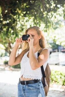 Weiblicher wanderer, der draußen steht, foto von der digitalkamera machend