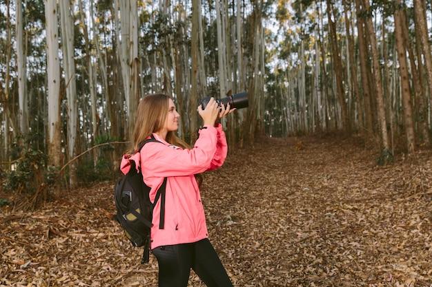 Weiblicher wanderer, der foto von bäumen des waldes macht