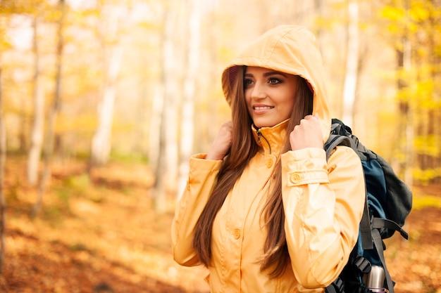 Weiblicher wanderer, der gegen regen schützt