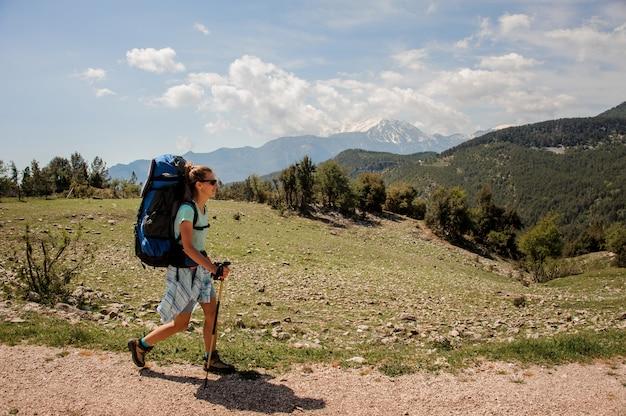 Weiblicher wanderer, der herauf die straße in den hügeln reist