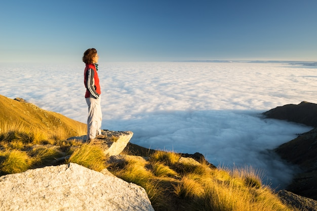 Weiblicher wanderer, der ihr ziel an der gebirgsspitze erreicht und ansicht der italienischen westalpen mit wolken auf dem tal unten betrachtet