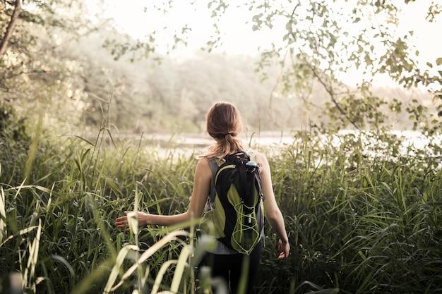Weiblicher wanderer, der in das grüne gras geht