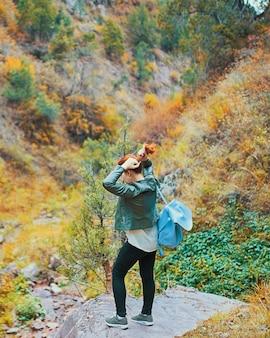 Weiblicher wanderer, der in gebirgswald geht.