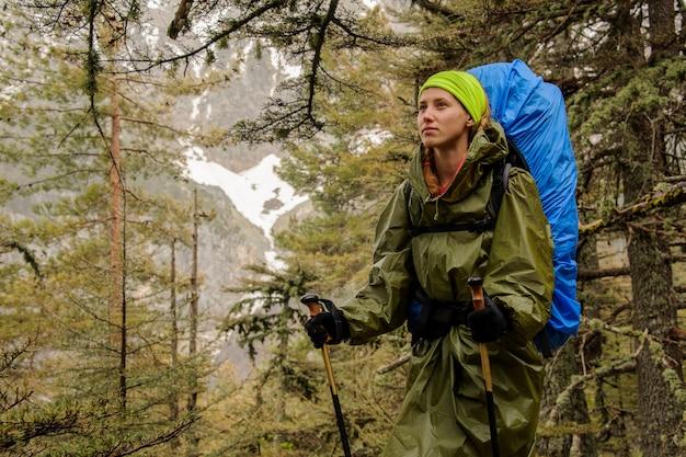 Weiblicher wanderer im regenmantel, der auf berg aufwirft
