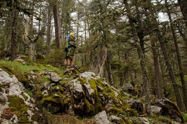 Weiblicher wanderer im regenmantel steht auf klippe