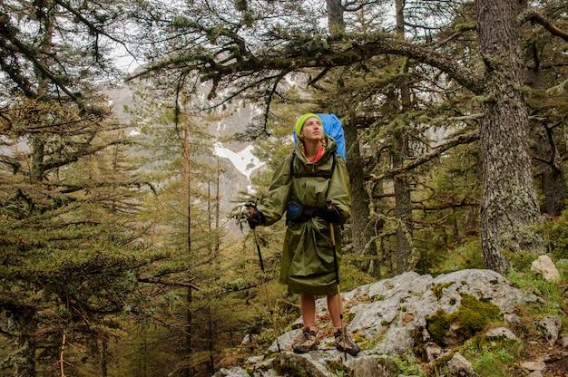 Weiblicher wanderer im regenmantel wirft auf felsen auf