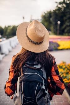 Weiblicher wanderer mit rucksack auf ausflug in touristenstadt, rückansicht. sommerwandern der jungen frau, wanderabenteuer