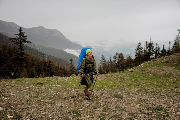 Weiblicher wanderer mit rucksack geht auf hochebene