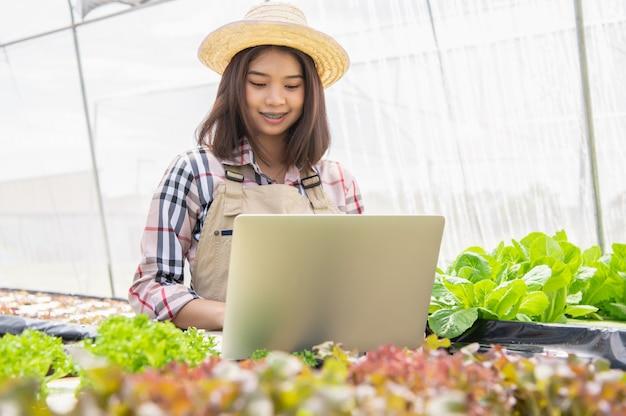 Weiblicher wasserkulturlandwirt, der gemüsewachstumsinformationen sammelt und laptop verwendet