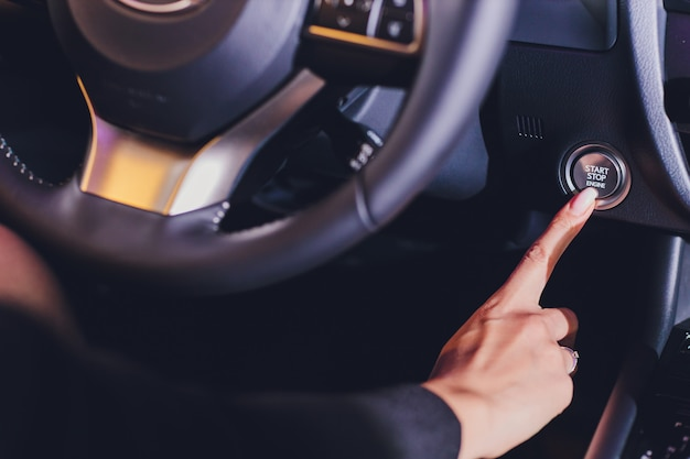 Weiblicher weiblicher finger, der den motorstartstoppknopf eines autos drückt.