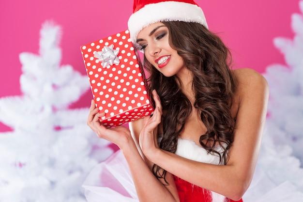 Weiblicher weihnachtsmann, der mit geschenk aufwirft