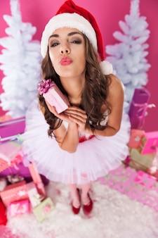 Weiblicher weihnachtsmann, der mit geschenken aufwirft