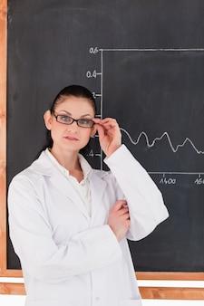 Weiblicher wissenschaftler, der nahe der tafel steht