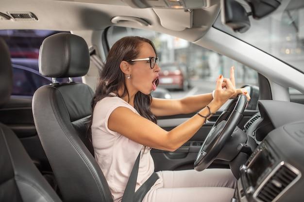 Weiblicher wütender fahrer, der beim fahren auf einem parkplatz mittelfinger zeigt.