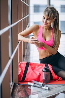 Weiblicher yogatrainer, der telefon verwendet