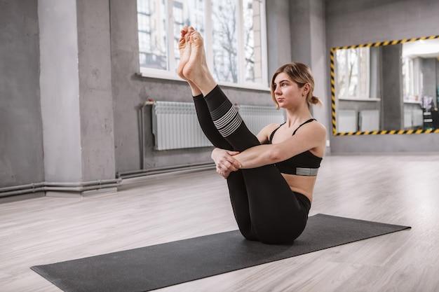 Weiblicher yogi, der trainiert, ausgleichende asanas tut