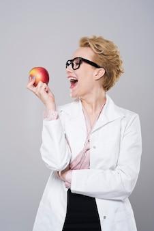 Weiblicher zahnarzt beißt köstlichen apfel