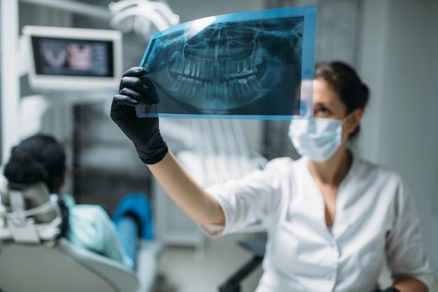 Weiblicher zahnarzt, der auf röntgenbild, zahnklinik, patient im stuhl auf hintergrund schaut. frau im zahnarztschrank, stomatologie, zahnpflege