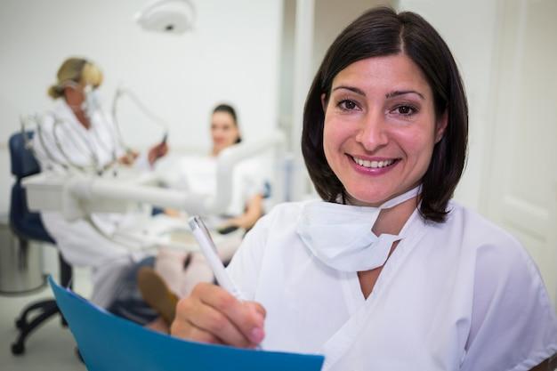 Weiblicher zahnarzt, der bericht in der zahnklinik schreibt
