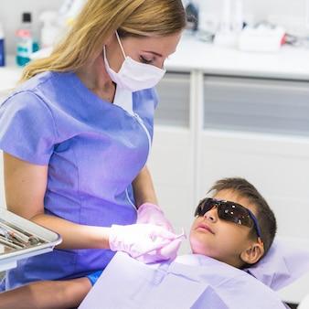 Weiblicher zahnarzt, der die zähne des jungen mit zahnmedizinischem spiegel überprüft