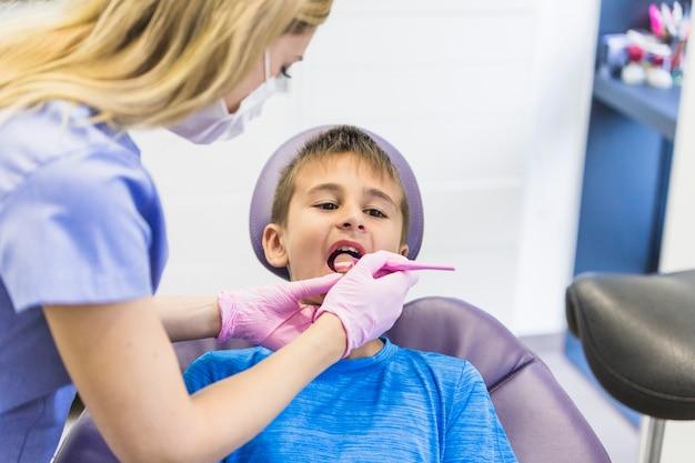 Weiblicher zahnarzt, der die zähne des kinderpatienten mit zahnmedizinischem spiegel überprüft