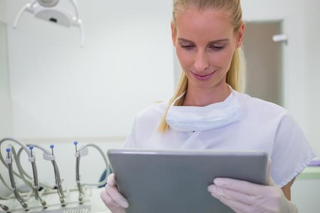 Weiblicher zahnarzt, der eine digitale tablette verwendet