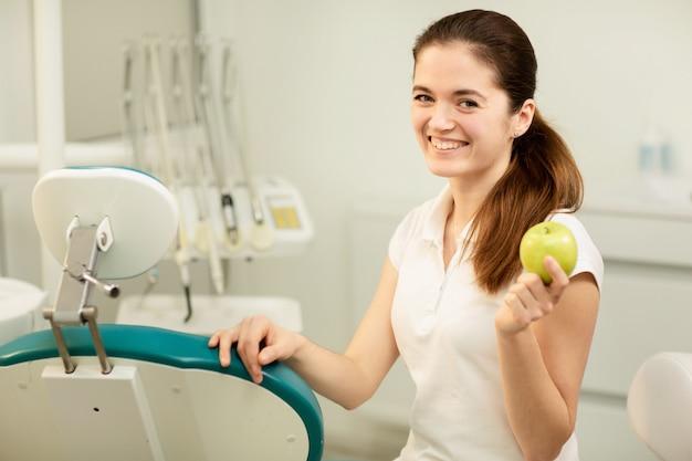 Weiblicher zahnarzt, der einen grünen apfel lächelt und hält