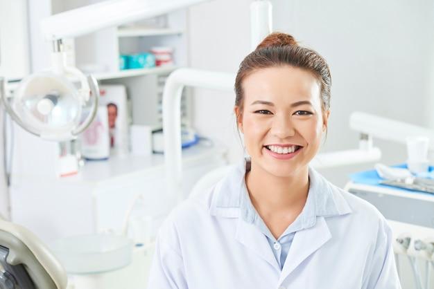 Weiblicher zahnarzt, der kamera anlächelt