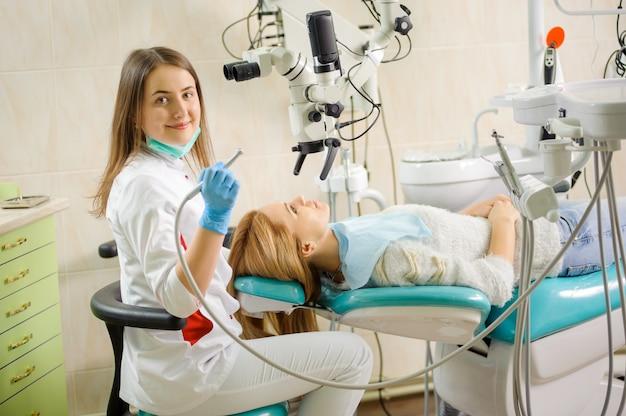 Weiblicher zahnarzt, der karies unter verwendung des mikroskops im zahnarztbüro behandelt