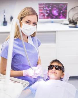 Weiblicher zahnarzt, der nahen tragenden sicherheitsschutzgläsern des jungen steht