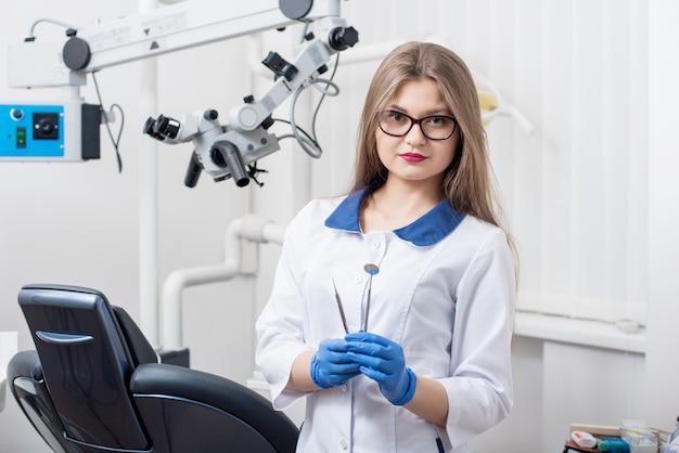 Weiblicher zahnarzt, der zahnärztliche werkzeuge an der morden zahnarztpraxis hält
